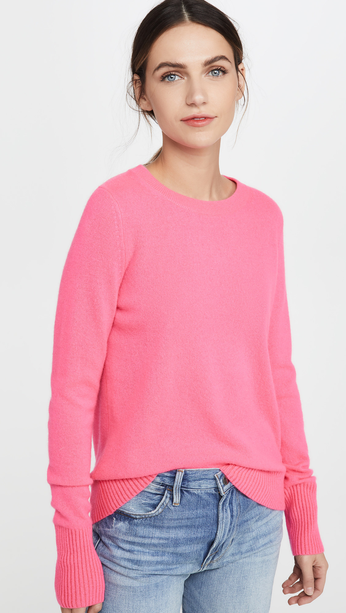 a model wearing a bright pink long sleeve cashmere sweater