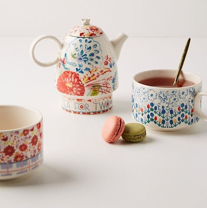 "a porcelain tea pot with a lid and a multi-colored floral print on it. It says ""tea for two"" along the bottom. Two mugs with colorful floral prints are sitting beside it."