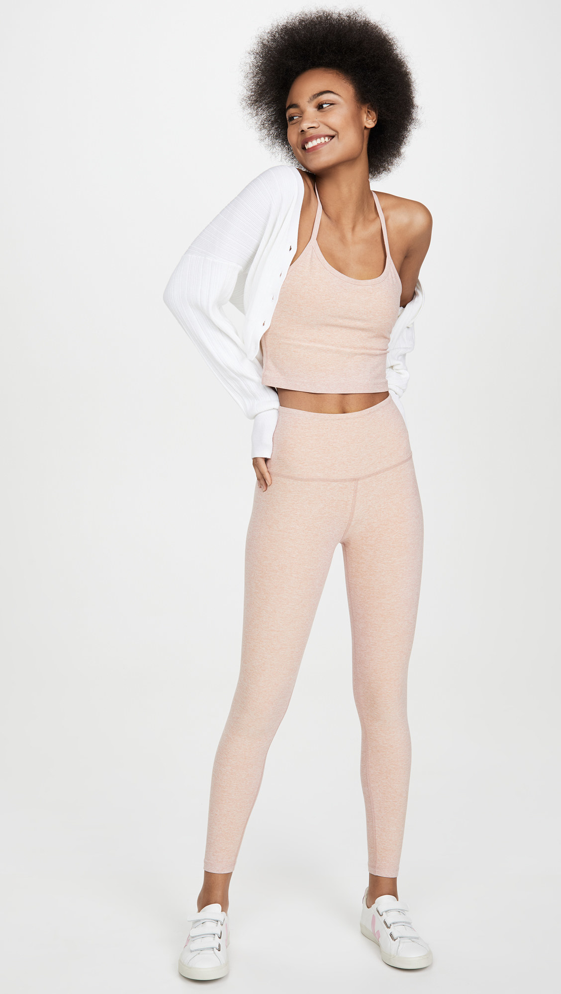 a model wearing heathered blush pink yoga pants with a matching tank top