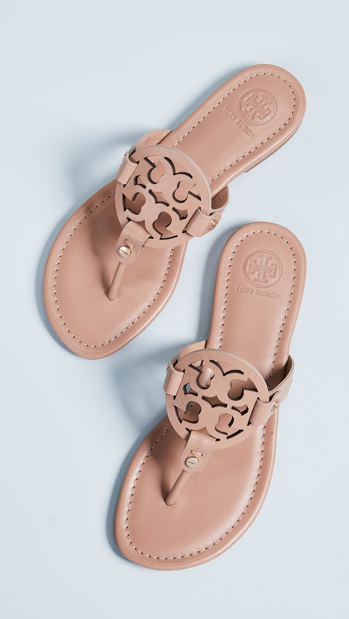 thong sandals in a nude color with the straps connected to a circular tory burch logo