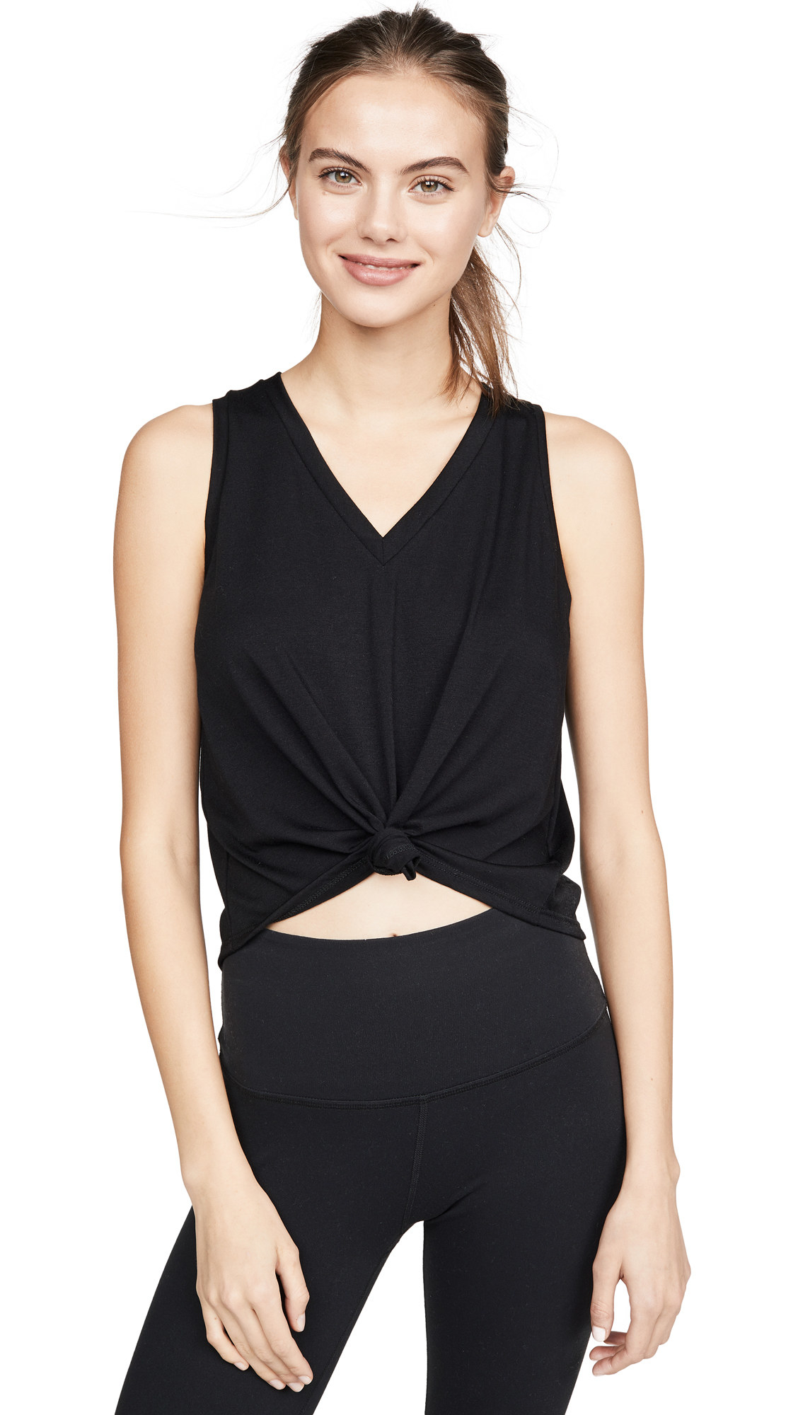 a model wearing the sleeveless top in black: it has a knotted middle that shows a bit of stomach