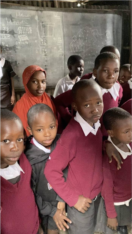 8th grade classmates wearing red sweaters inside a corrugated metal shack, Mukuru slum, Nairobi