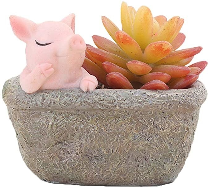 the planter with a little pig leaning on the side