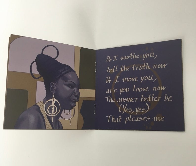 a zine flipped open to show one side of the page with an animated version of Nina Simone wearing a braided updo and large gold dangling earrings and the other side has lyrics of hers written on it