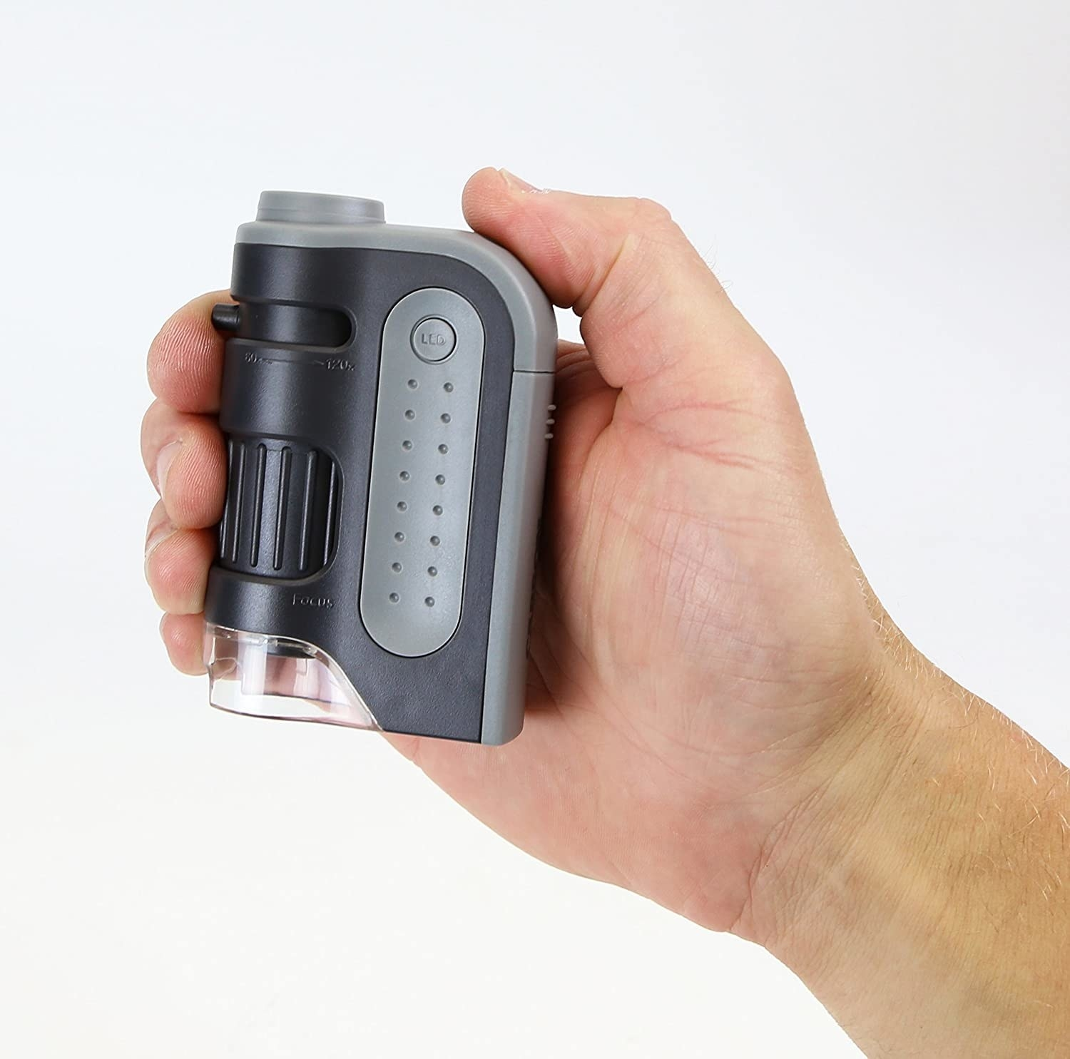 A hand holds up the pocket sized microscope against a plain background to demonstrate its small size