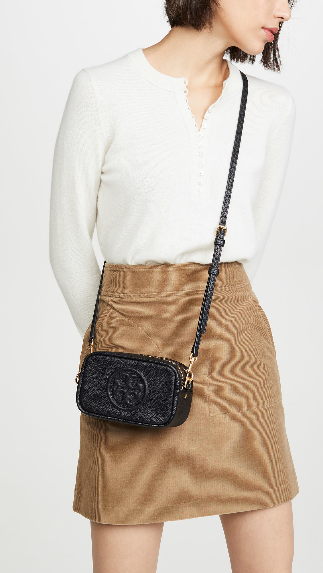 a model wearing the bag slung across her body: it's small, made of black leather, has a rounded rectangle shape and the Tory Burch logo imprinted in the middle. the zipper is gold