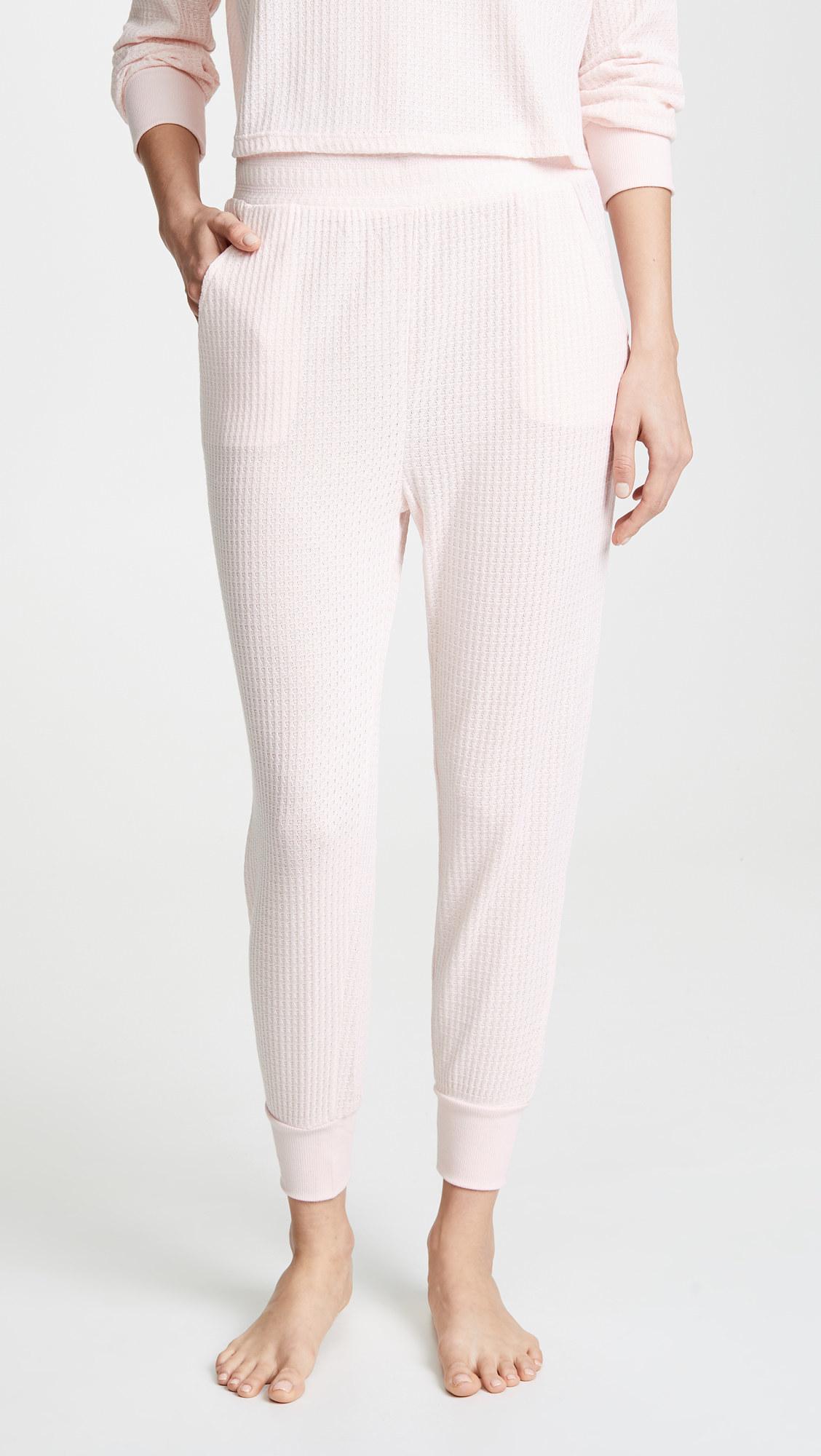 a model wearing blush pink waffle knit pants with cuffed bottoms and a thick waist band
