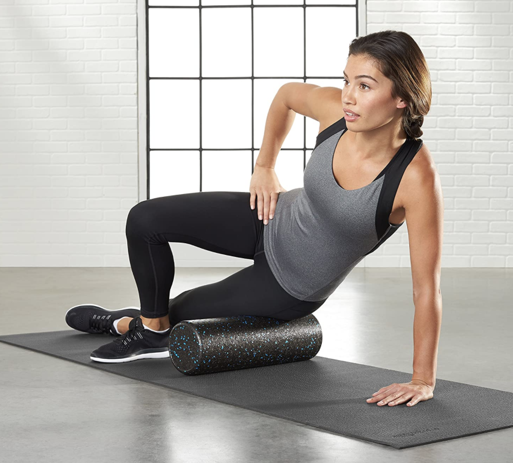 Model using a black foam roller with blue speckles on their upper thigh