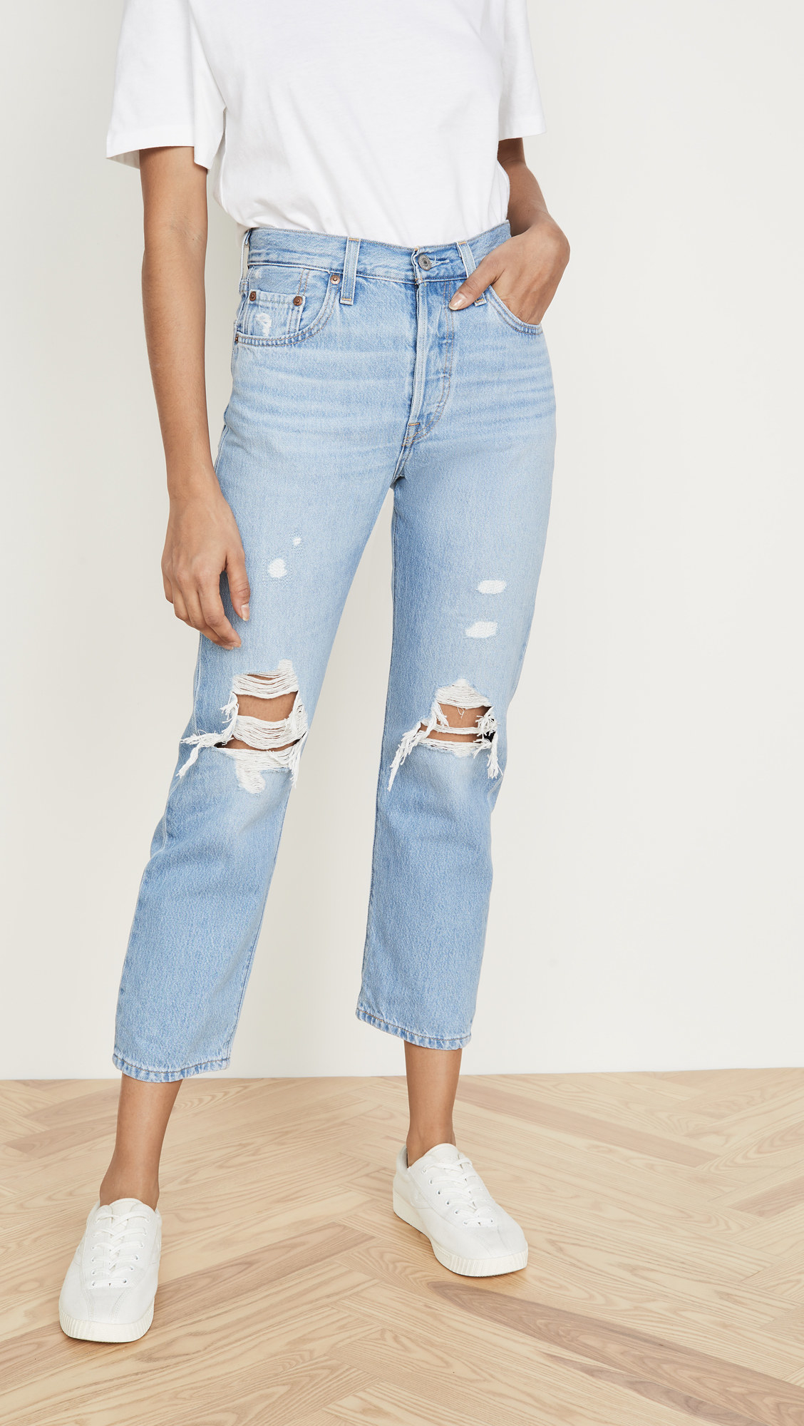 a model wearing light wash cropped denim jeans with distressed knees