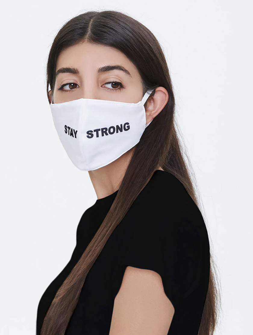 """Model in a white mask that says """"Stay Strong"""" in black letters"""