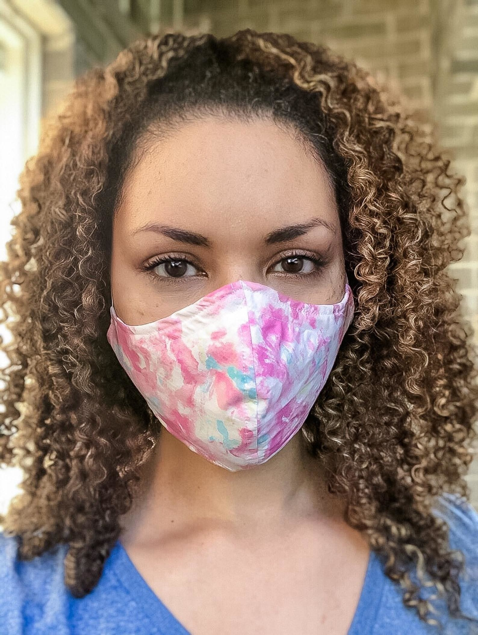 A model in a pink and blue watercolored face mask