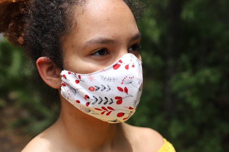 A model in a white face mask with red floral patterns