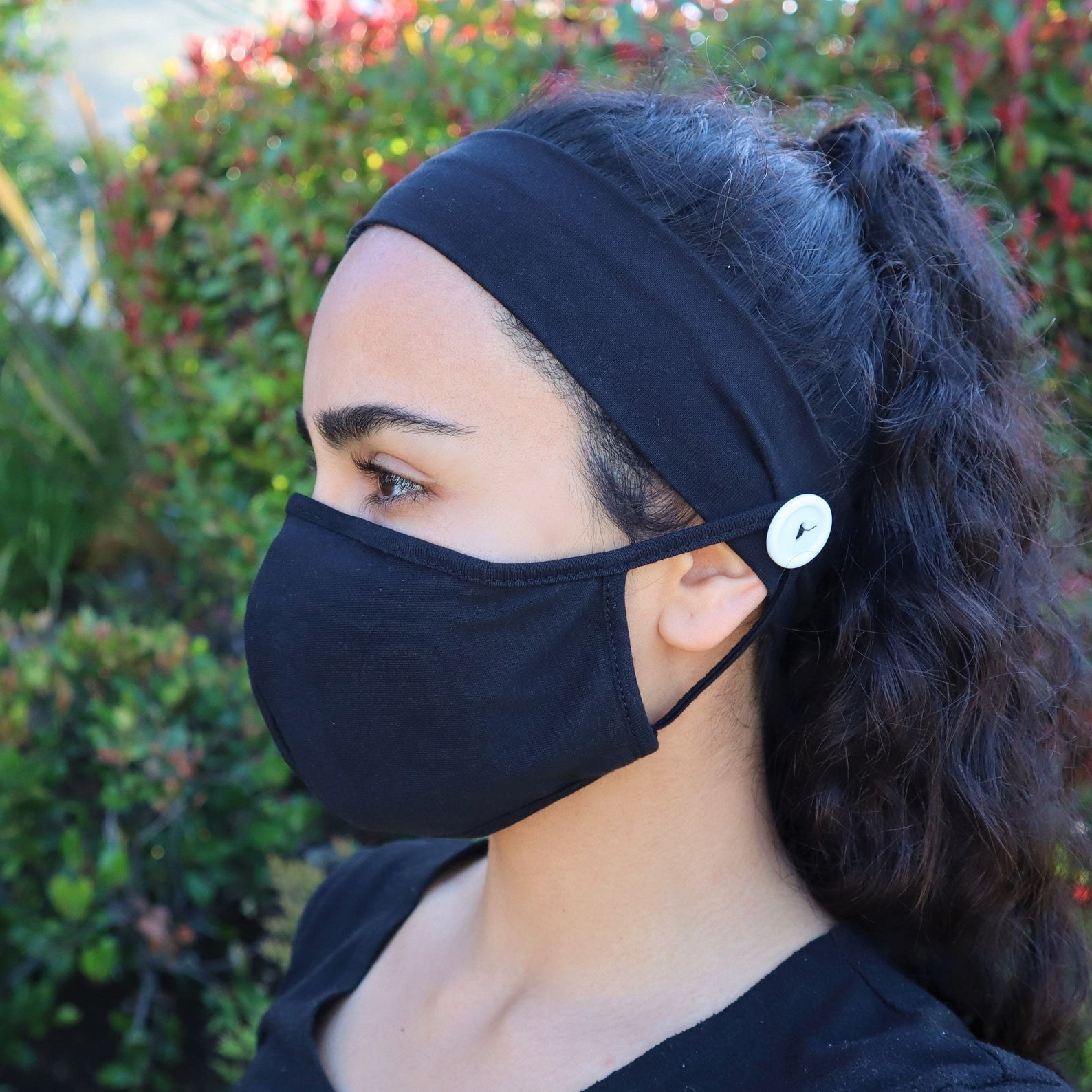 A model in a black face mask attached with to button on a headband