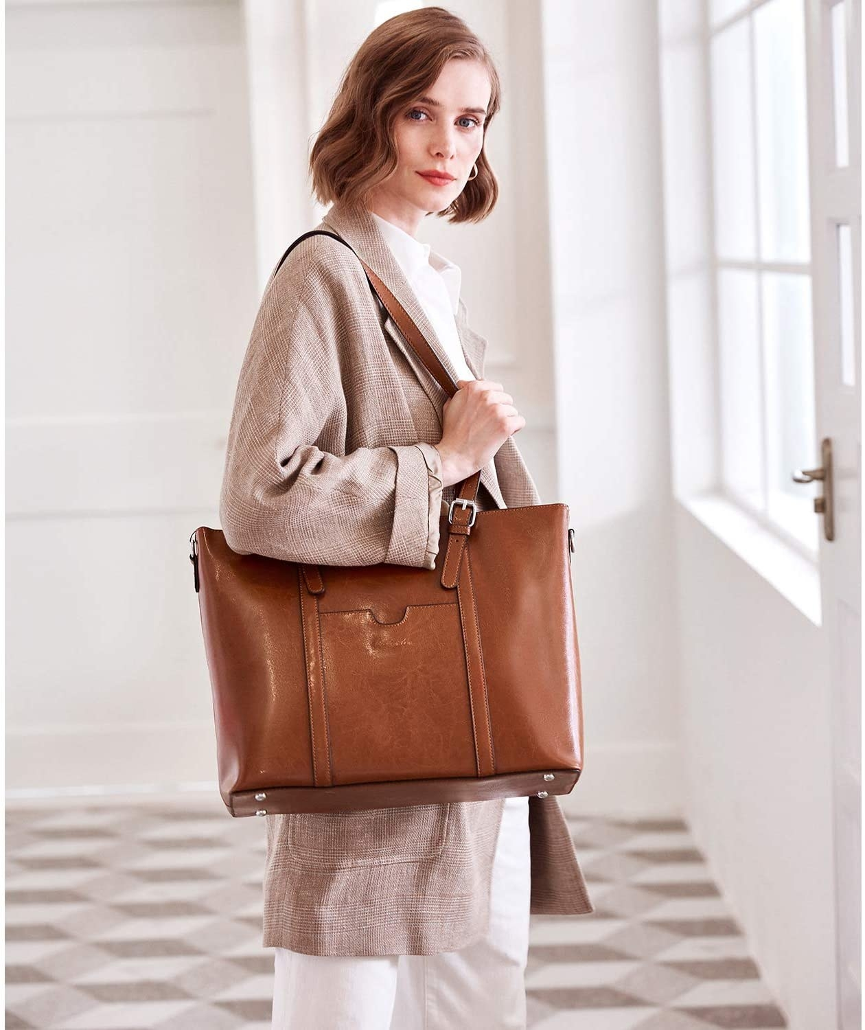 A model holding a tote bag across her shoulder