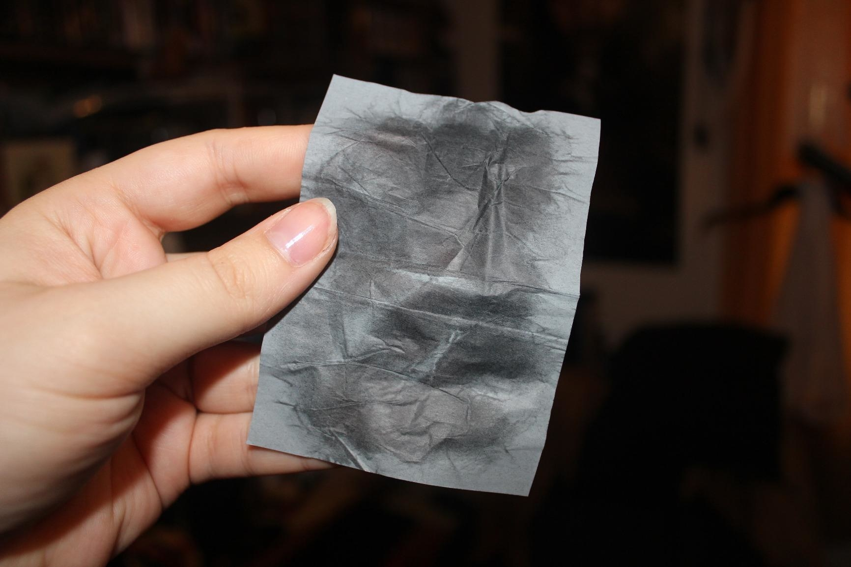 A hand holding a blotting sheet that appears to have absorbed oil