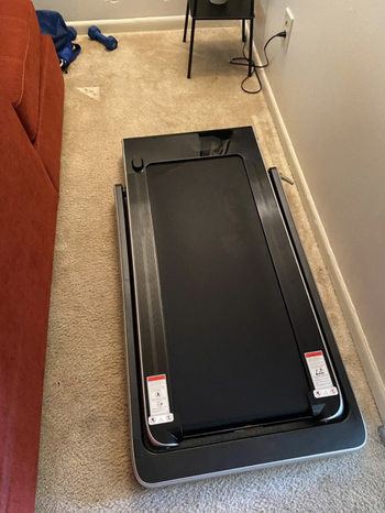 Reviewer's folded treadmill open and ready to use in their bedroom