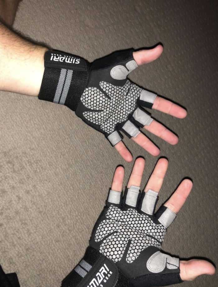 Reviewer wears a pair of black and gray workout gloves on their hands