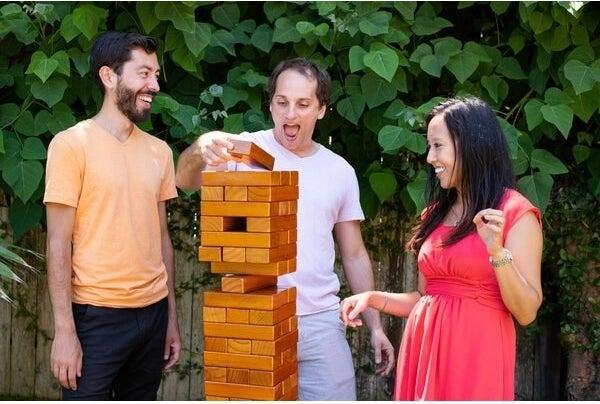 three people playing a giant Jenga-like game outside