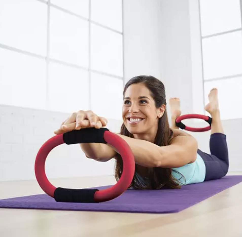 Model works out with pink Pilates rings on a purple mat