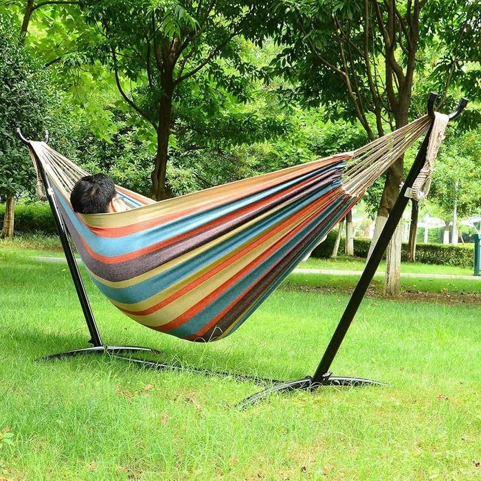 A person lying down in a self-supporting hammock outside