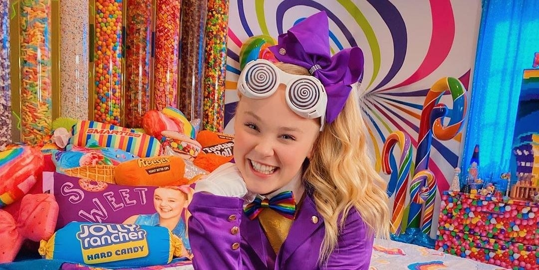 JoJo Siwa looking like Willy Wonka surrounded by a plethora of candy and candy themed decor