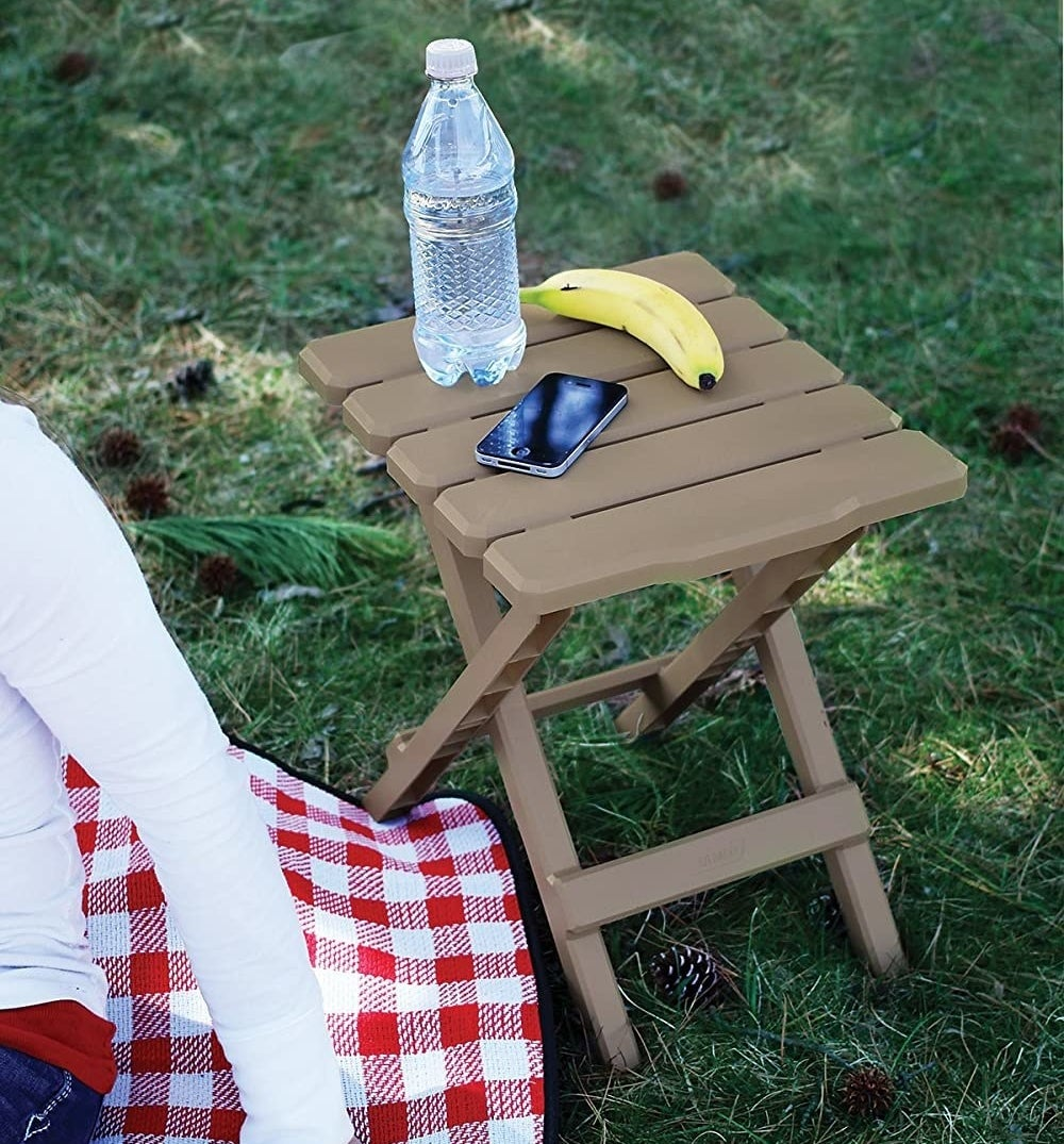 A small table with some water, a phone, and a banana on it