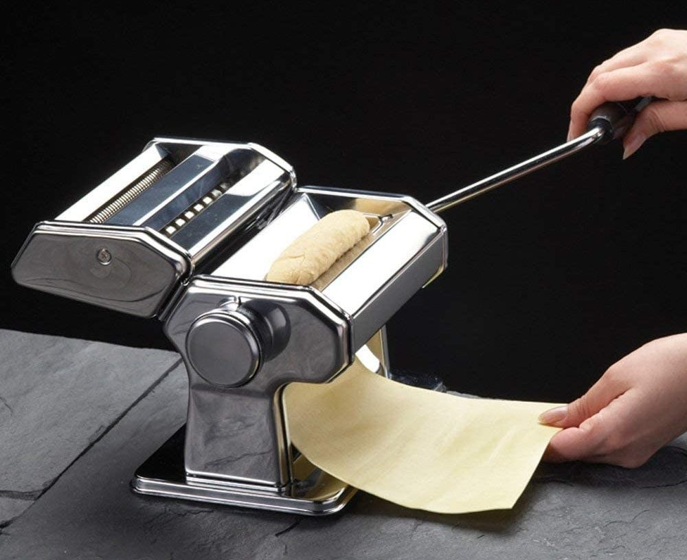 A sheet of pasta being passed through a pasta machine