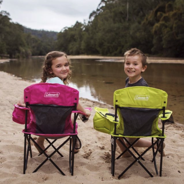 Two children turning around in collapsible outdoor chairs to smile at camera