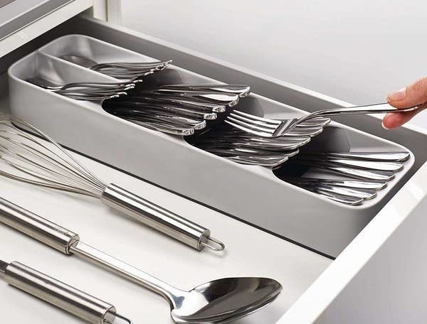 person putting a fork into the gray cutlery organizer