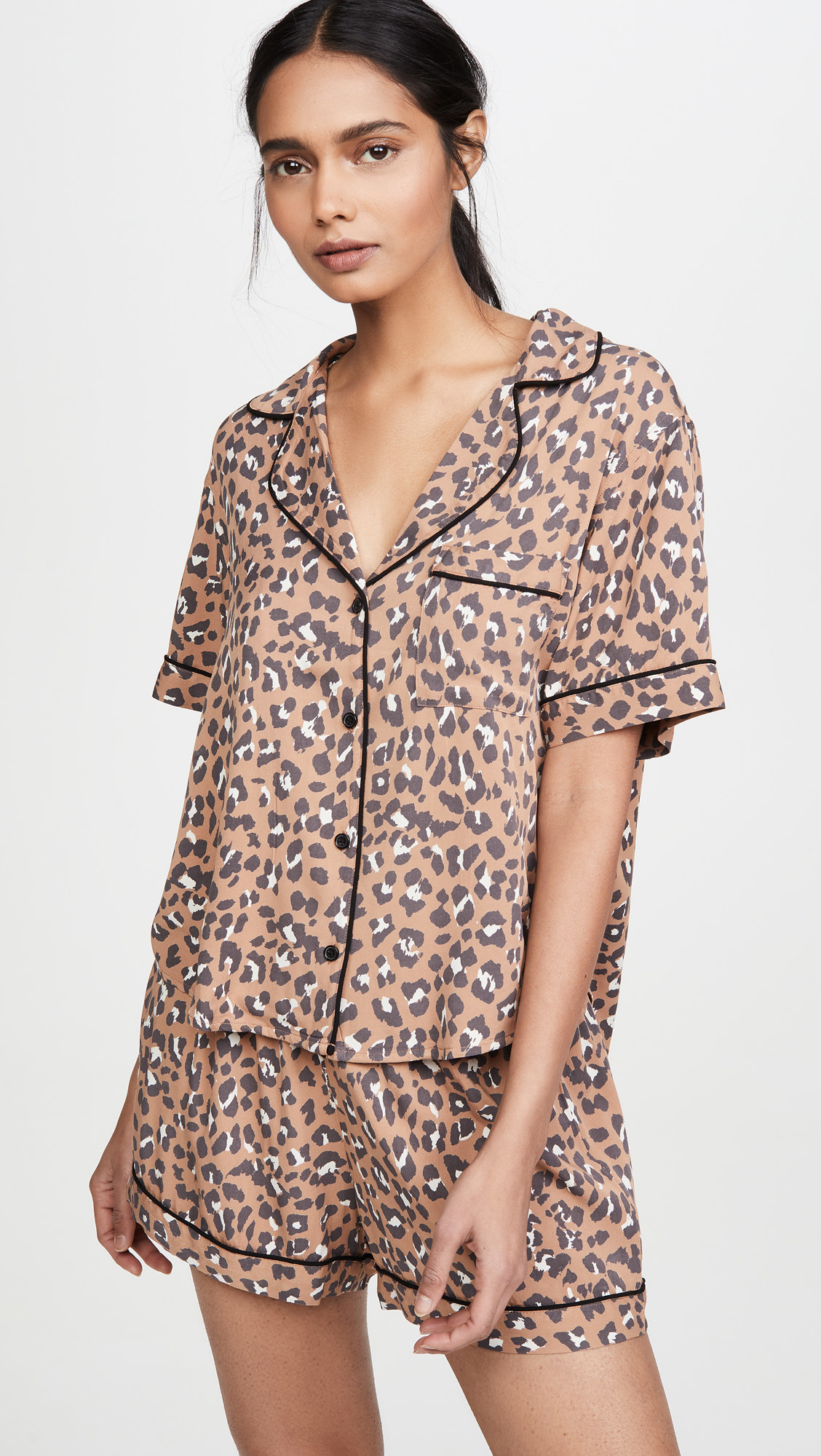 model wearing tannish-brown leopard print pajamas: the top is short sleeves with a collar and has buttons in black down the middle, the bottoms are shorts and match