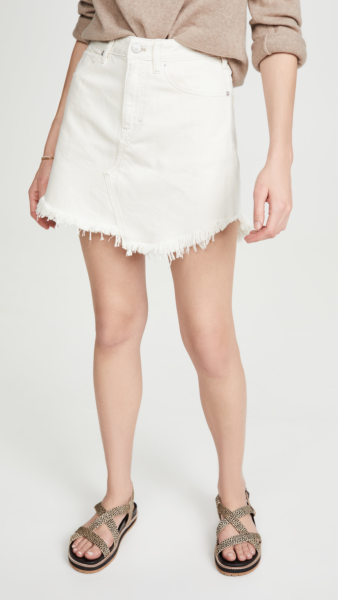 a model wearing the white denim skirt which has a diagonal seam down the bottom, middle