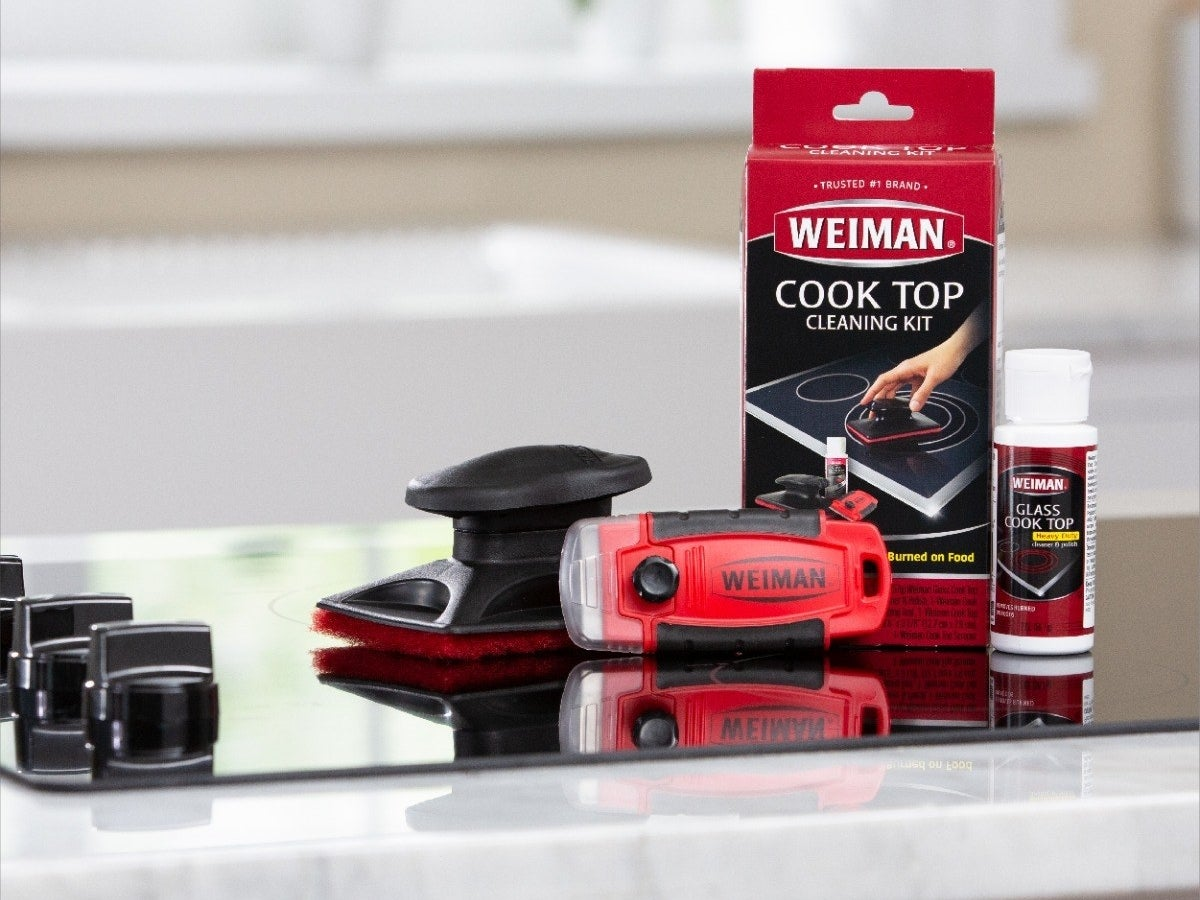 The brush, razor, and glass cooktop cleaner sitting on top of a stove