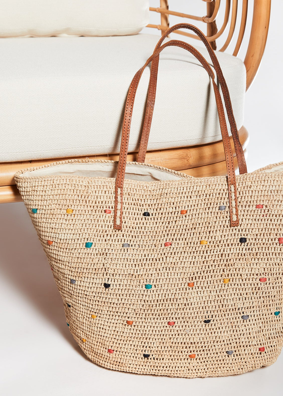 the woven bag with a rainbow of colors stitch throughout the natural colored material