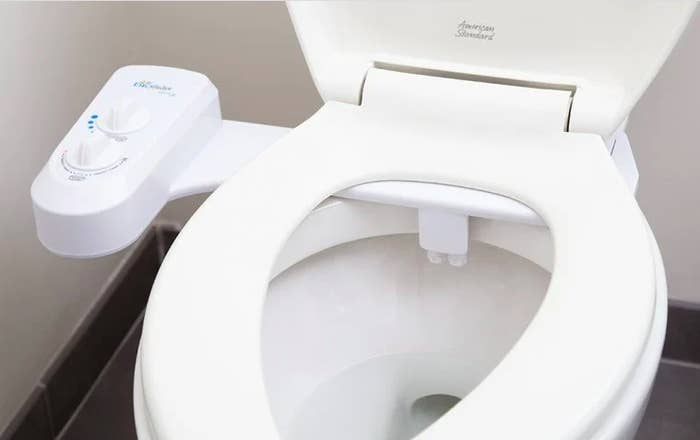 toilet with a white rectangular-shape attachment on side with dials and a piece at the top/back of the toilet bowl that sprays the water