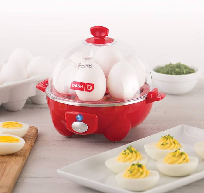 An egg cooker with six eggs sitting inside of it with the lid on
