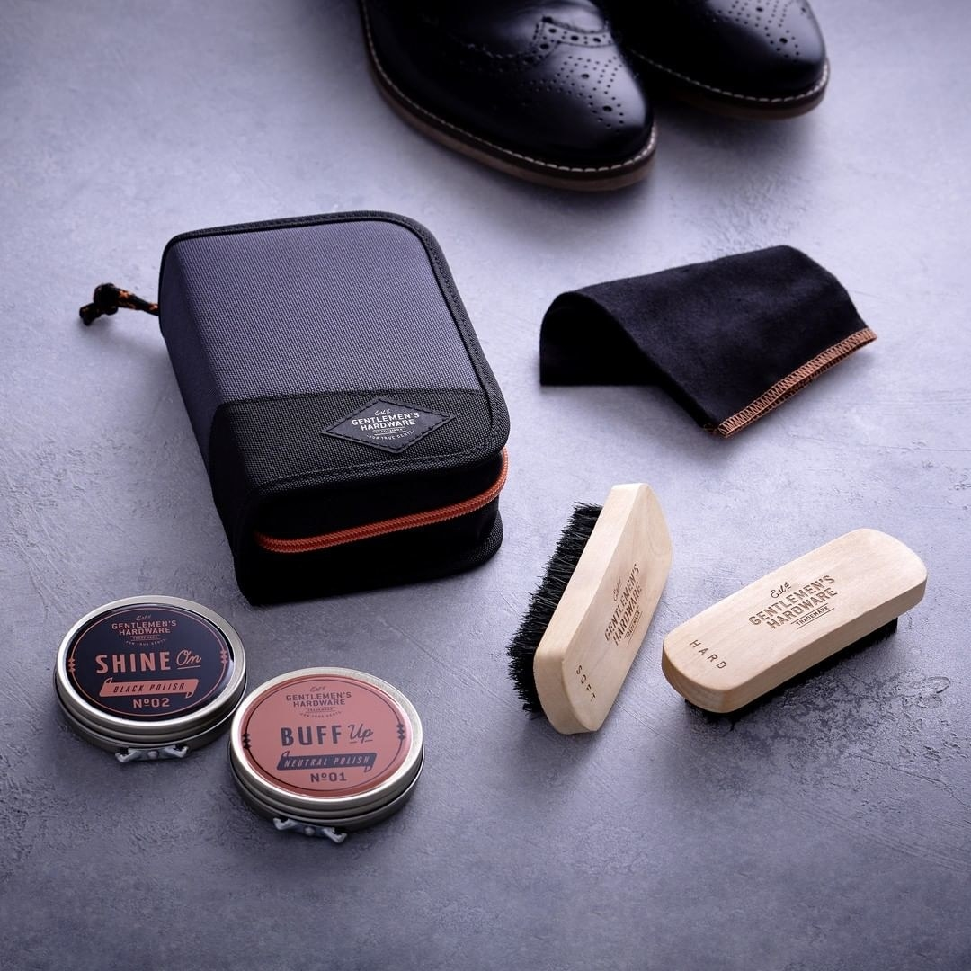 The kit lies next to a pair of brogue shoes, where two brushes, two polishing products, and a soft cloth are visible