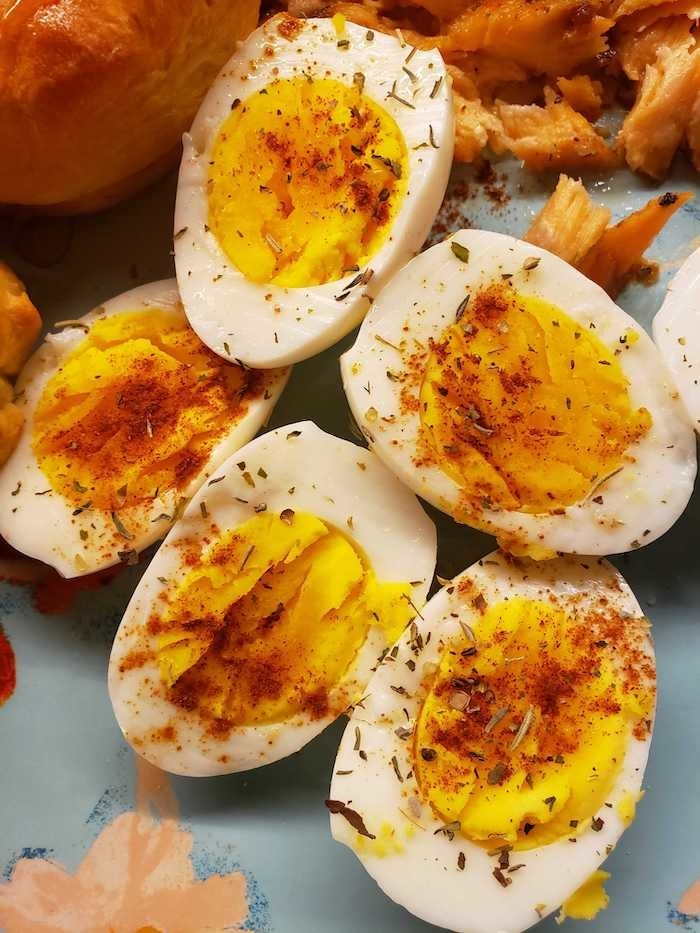 five halves of hard-boiled eggs with spices on top