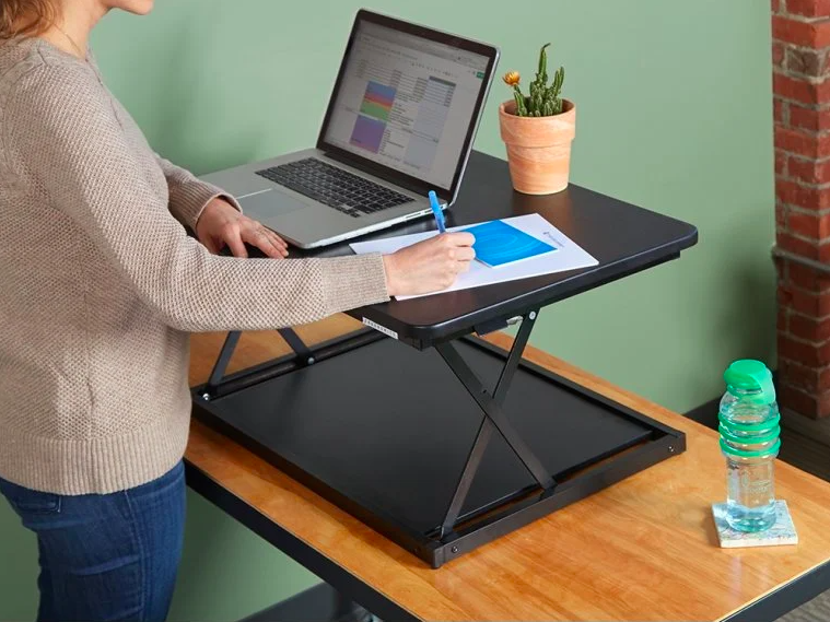 person on a table with desk lift with laptop on it with room to write on a sheet of paper on surface