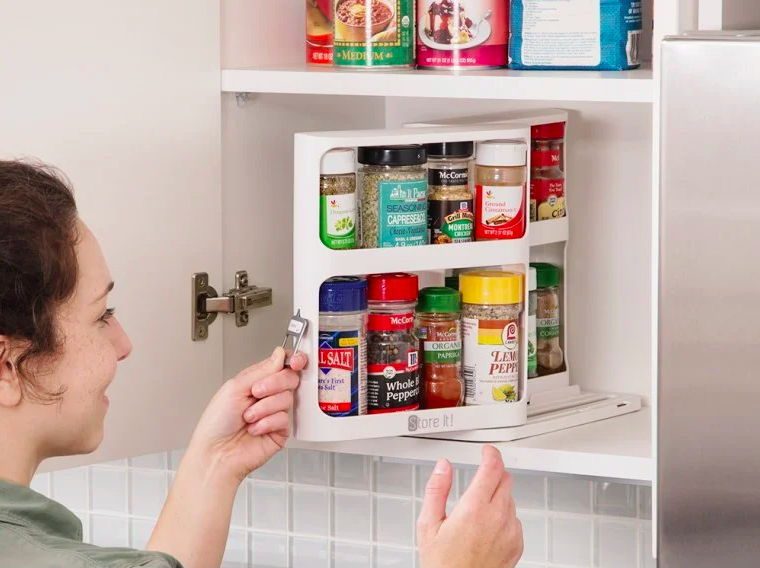 person pulling one of the organizers with two shelves of spices out of a kitchen cabinet
