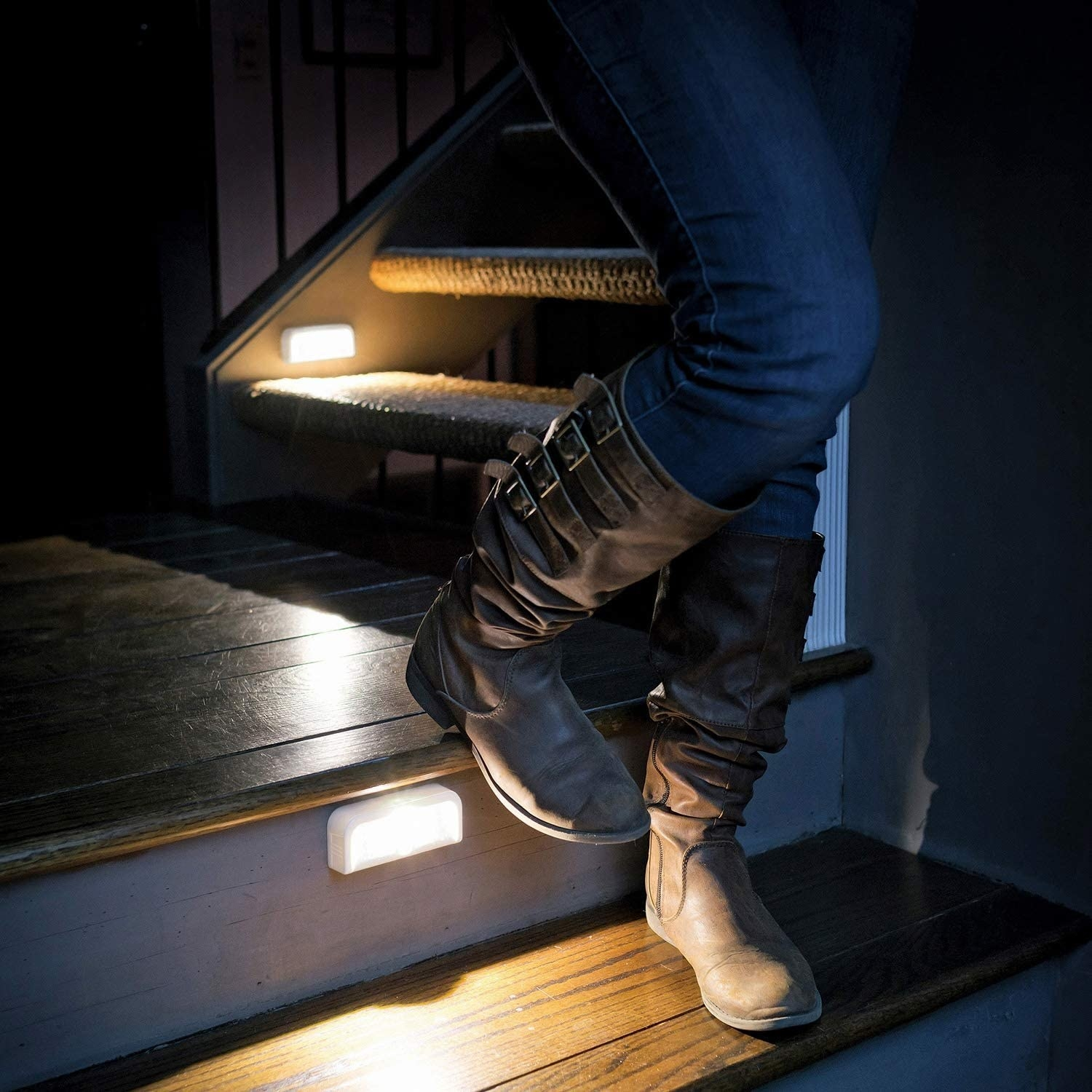 A person walking up dark stairs with the stick-on lights on them