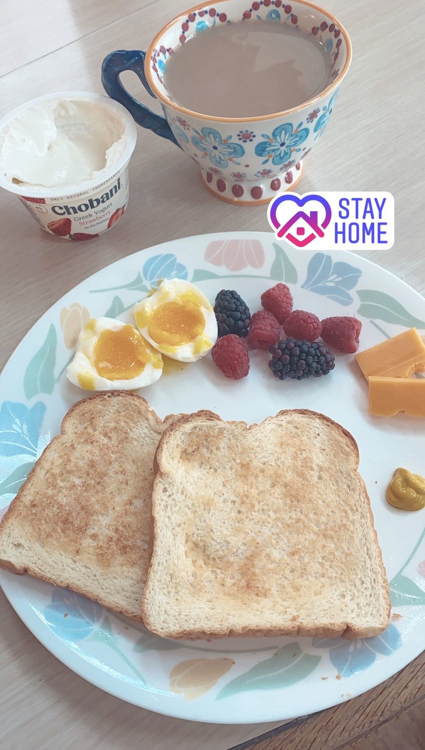 two halves of one boiled egg on a plate with plain white toast, berries, and slices of cheese