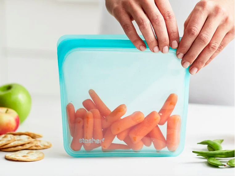 person closing the silicone bag with baby carrots inside
