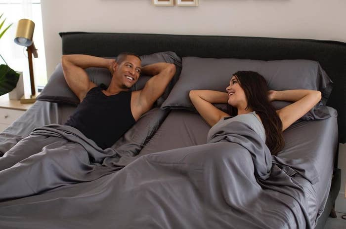 a couple laying in bed with gray sheets