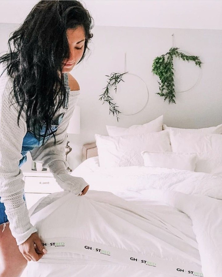 a model making a bed with the white ghostbed sheets
