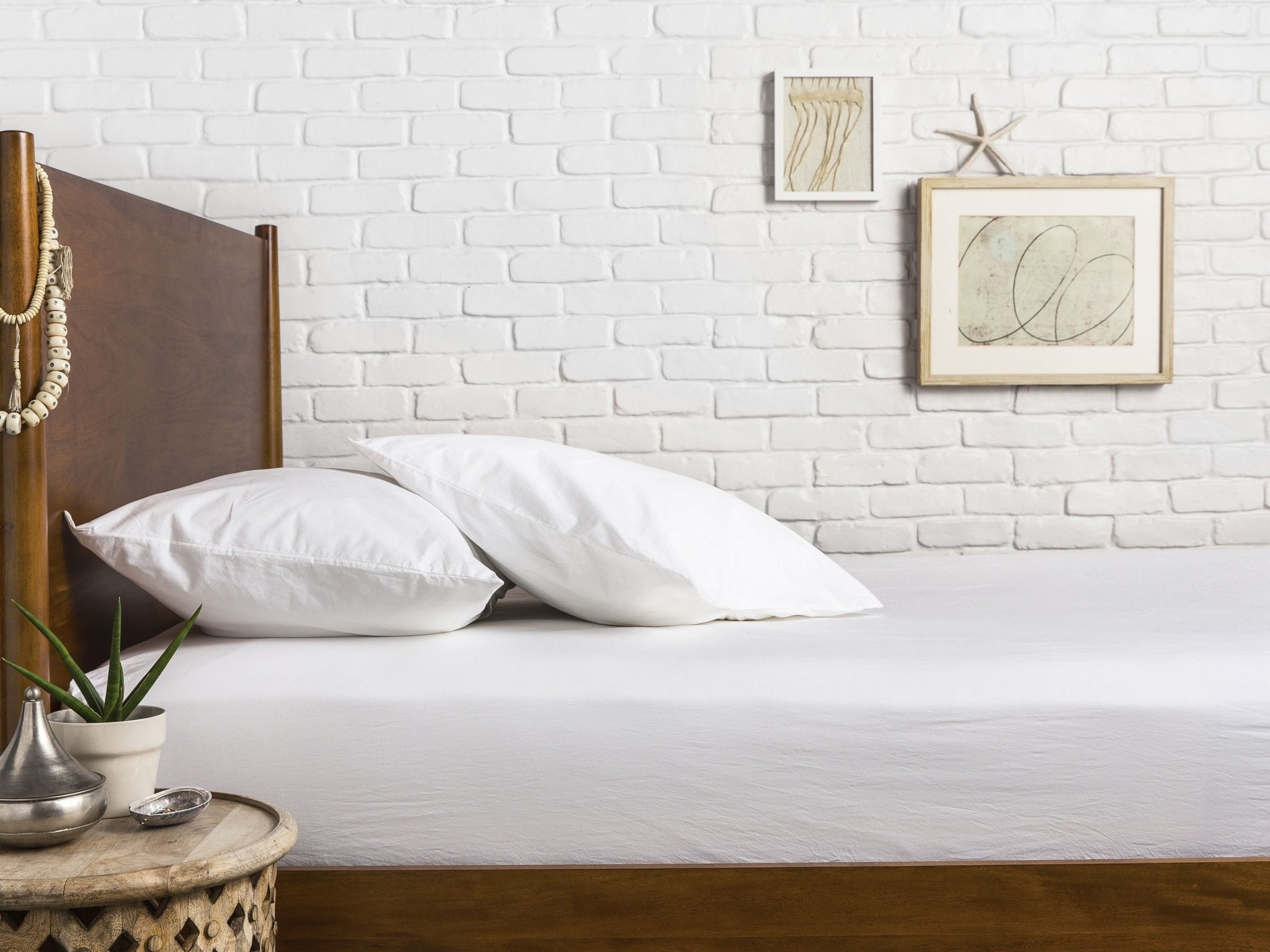 a bed with white sheets and white pillowcases on it