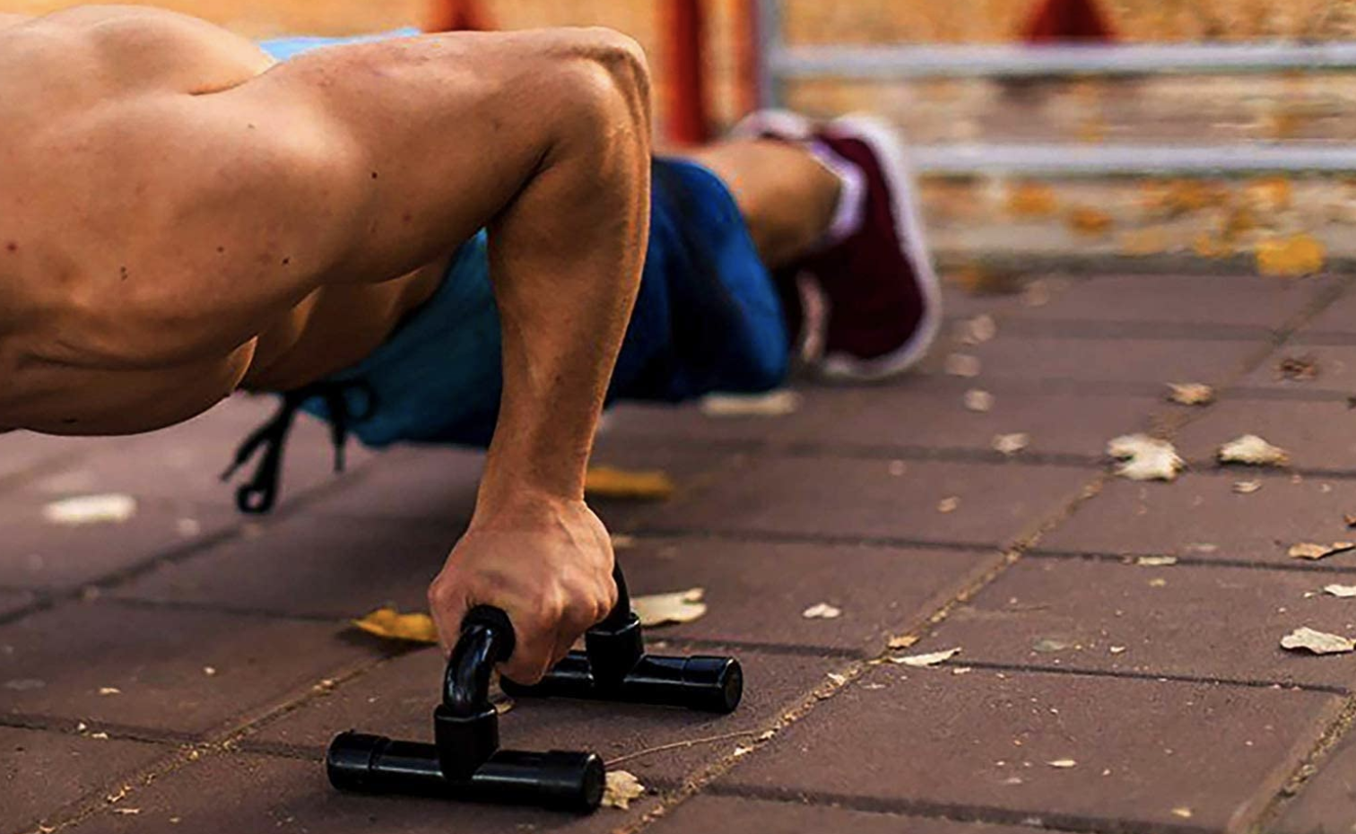 A model uses black push-up bars while exercising on an outdoor patio