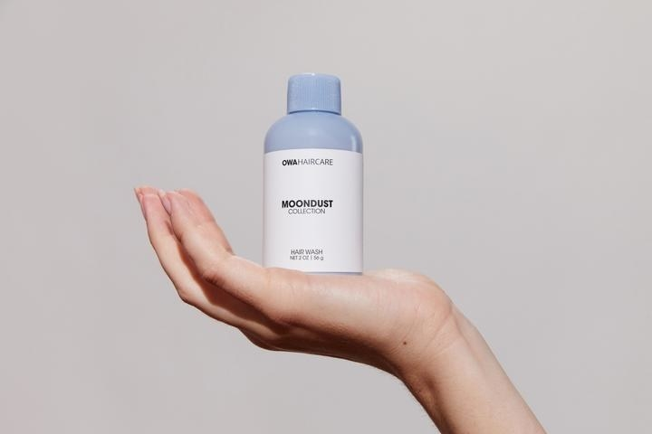 """hand holds small blue bottle that says """"moondust"""""""