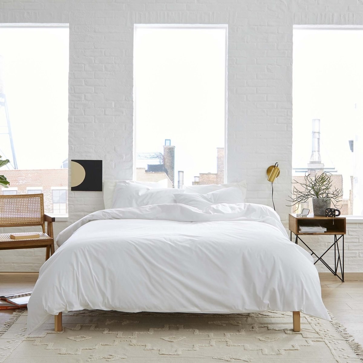 a bedroom with bright windows showcasing a cozy bed with a white comforter and white sheets