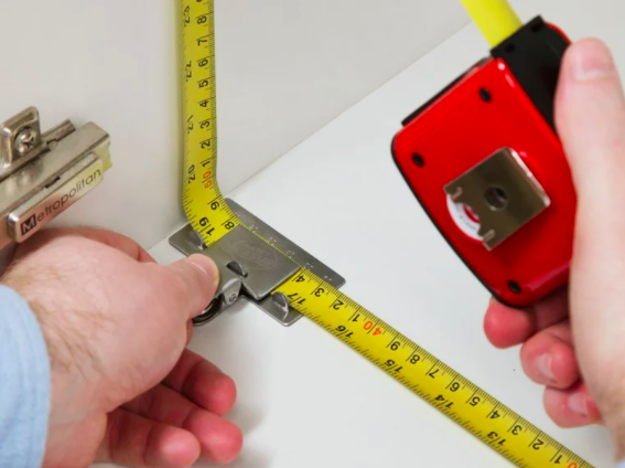 binder clip like metal clip holding a tape measure in place up against a corner inside a cabinet