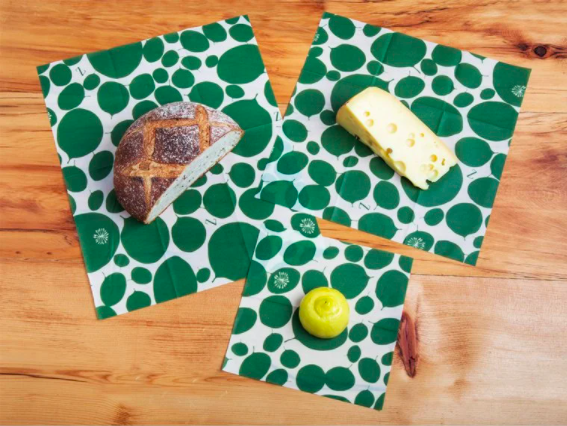 flat beeswax wrap pieces with a slice of bred, cheese, and half a lemon on it